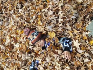 LSA 2018 Harvest Fest - student smiling while buried in leaves