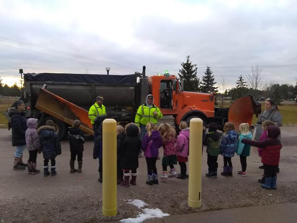 Group of students listening to a Road Commission member about plow safety