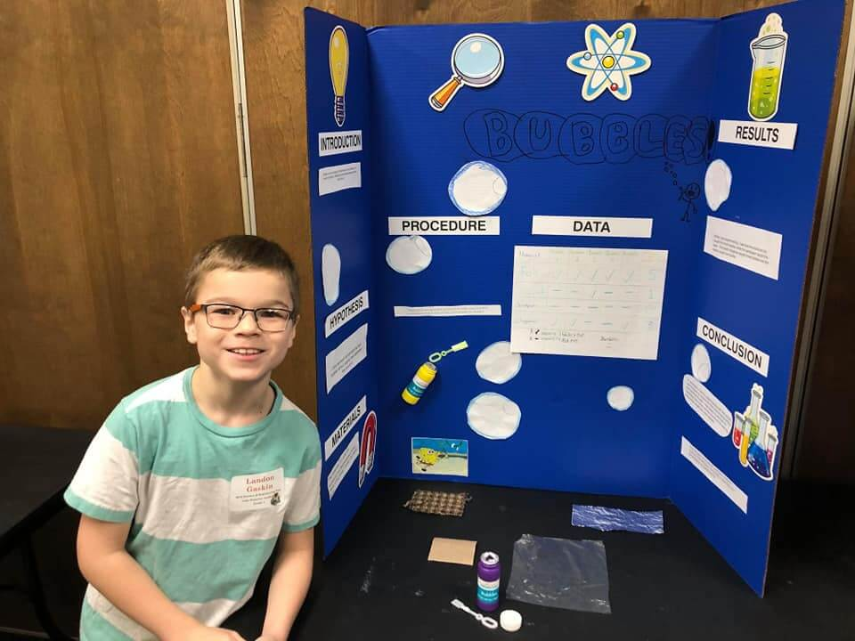 Student standing in front of his Science Fair project smiling