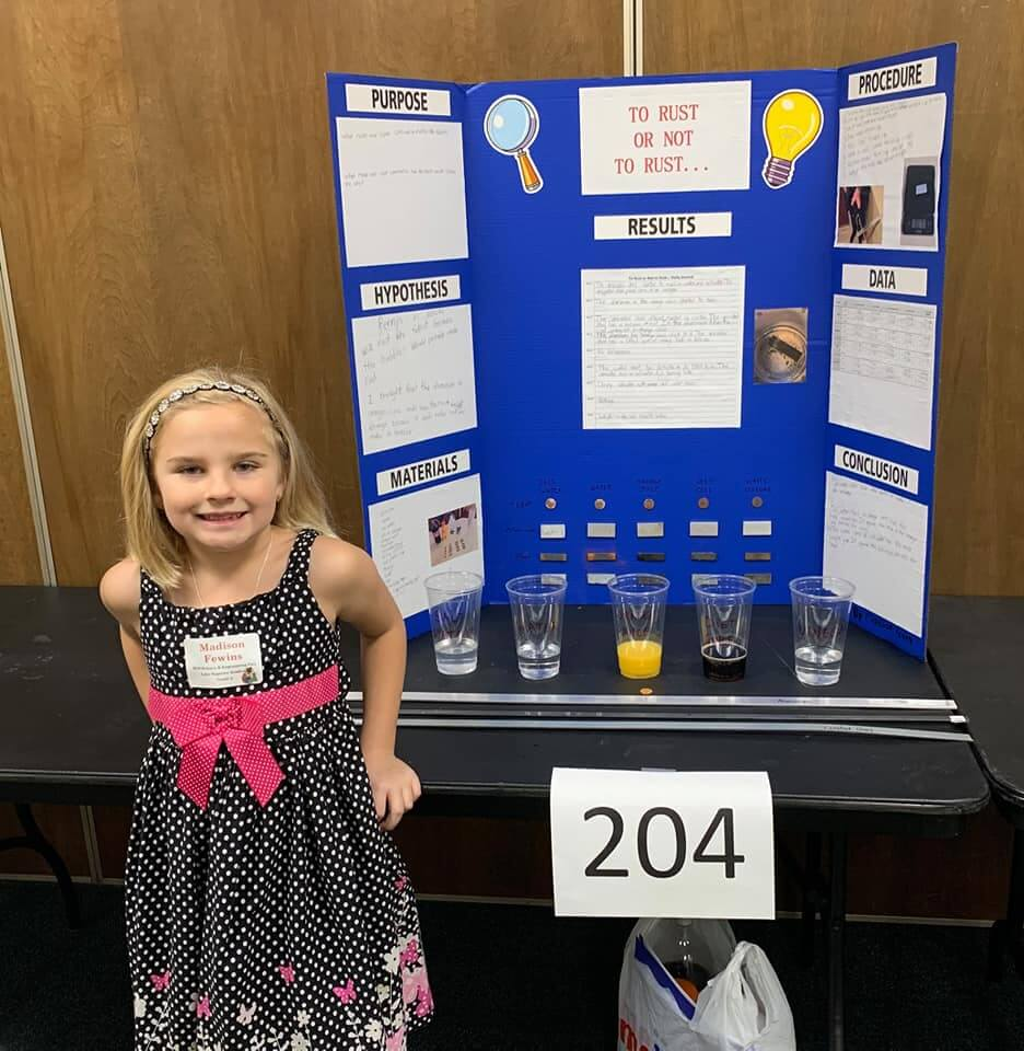 Student standing in front of her Science Fair project smiling