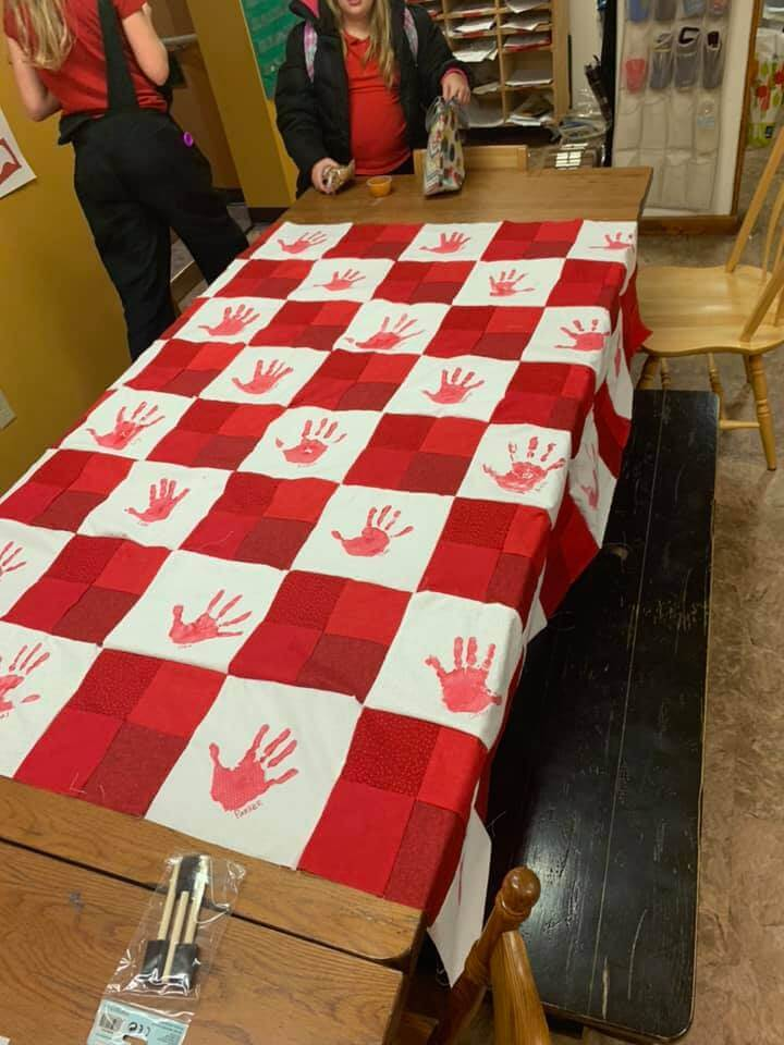 Red handprint quilt almost completed