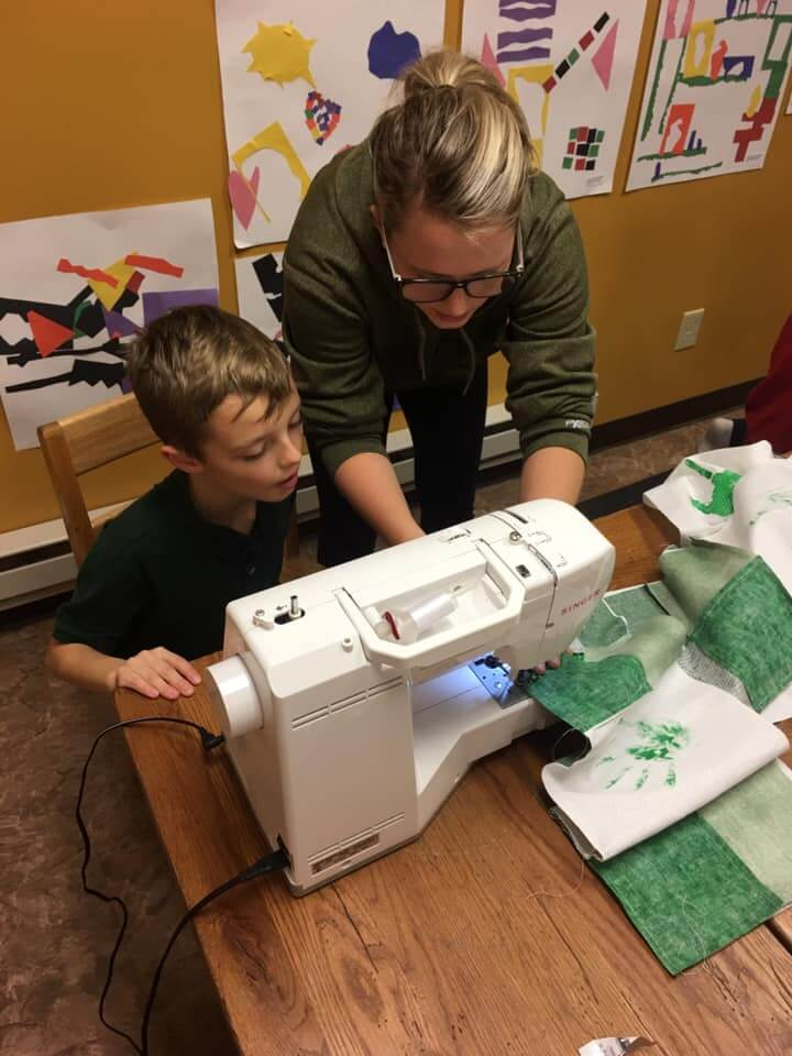 Ms. Erin helping students sew with a sewing machine