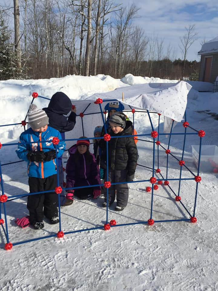 Students outside building an igloo structure